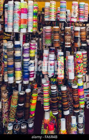 Viele verschiedene bunte Armbänder in den Souvenir-Shop auf Papierrollen - Stockfoto