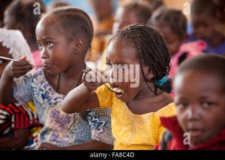 Kindergartenkinder Essen zu Mittag in der Kouka Primary School in Kouka Abteilung, Burkina Faso. - Stockfoto