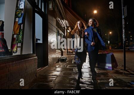 Frontansicht der paar Arm in Arm hinunter street Shopping-Tragetasche in der Nacht, Window-shopping - Stockfoto