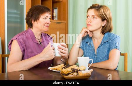 Junge Mädchen und die Mutter im Alter von Kaffee zu trinken und ein Schwätzchen indoor - Stockfoto