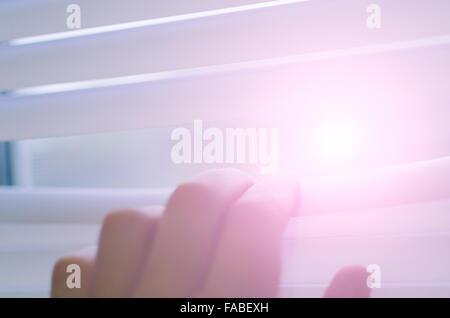 Männliche Hand, die Lamellen der Jalousien mit einem Finger, mit weichem Licht zu sehen, durch die Trennung - Stockfoto