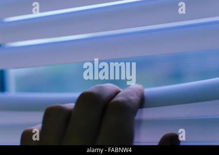 Hand, die Lamellen der Jalousien mit einem Finger zu sehen, durch die Trennung - Stockfoto