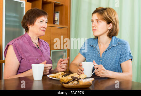 Junge Mädchen und ältere Mutter Kaffee zu trinken und ein Schwätzchen indoor - Stockfoto