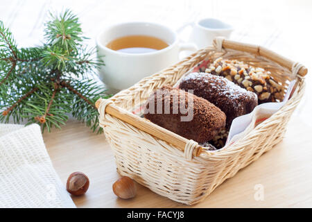 Frische heiße Grüntee in Glasschale mit Zitrone und Zimt, Kuchen Schokolade in Korb und Nüssen und Zimt im Glas - Stockfoto