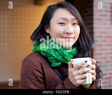 Junge asiatische Frau lächelt in die Kamera, während ihre Hände mit Tee in einen Pappbecher in den Winter-Straßen - Stockfoto