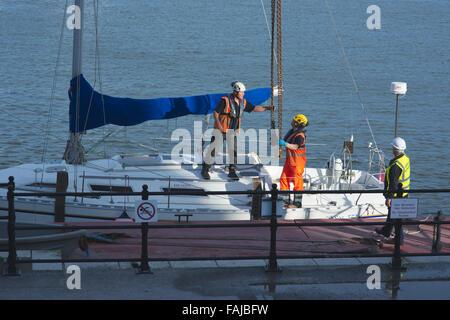 Drei Arbeiter befestigen Boot Hubketten zu Yacht in der Vorbereitung für das Heben von Wasser - Stockfoto