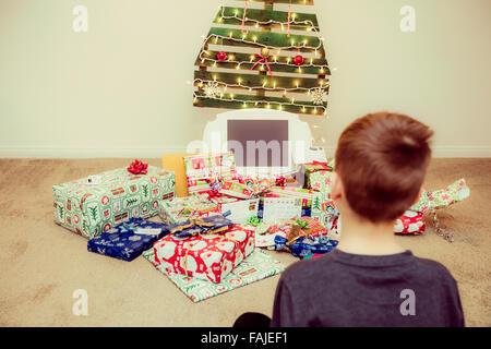 kleiner Junge schaut die Weihnachtsgeschenke unter einer ökologischen, wiederverwendbare Weihnachtsbaum - Stockfoto