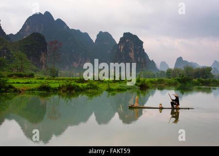 Fischer auf Bambus-Floß auf Mingshi Fluss mit Karst Hügeln bei Sonnenuntergang, Provinz Guangxi, China - Stockfoto