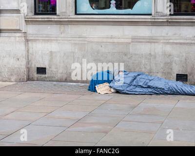 """Piccadilly, London, UK, 1. Januar 2016. Ein Mann liegt in einem Schlafsack, mit einem Schild """"Happy New Year - Ex - Stockfoto"""