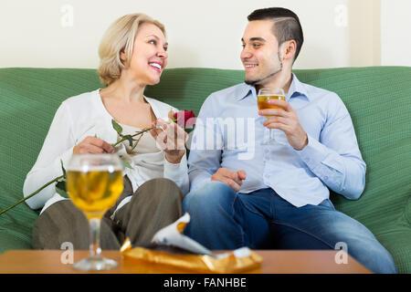 Lächelnd Reife Frau mit jungen Freund mit Date mit Wein im Haus - Stockfoto