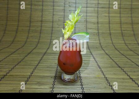 Bloody Mary oder blutige Caesar cocktail oder Glas Tomatensaft mit Limettenschnitz und Sellerie Stengel auf Bambusmatte. - Stockfoto