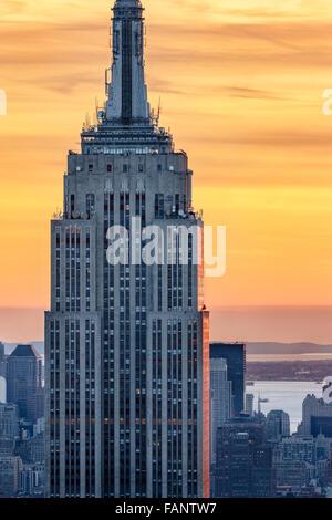 Luftaufnahme des oberen Teils der Wolkenkratzer Empire State Building bei Sonnenuntergang mit einem feurigen Himmel. Midtown Manhattan, New York City