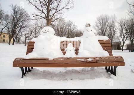 Der Schneemann auf einer Bank Familie: Vater, Mutter und Kind - Stockfoto