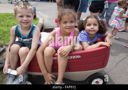 Drei Kinder in einem modernen Kunststoff Radio Flyer Wagen fahren. Große alte Straße Messetage. St Paul Minnesota - Stockfoto