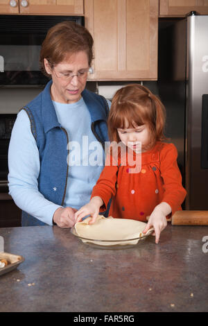 Vier Jahre altes Mädchen Kuchen Teig in Pfanne mit ihrer Großmutter helfen ihr platzieren - Stockfoto