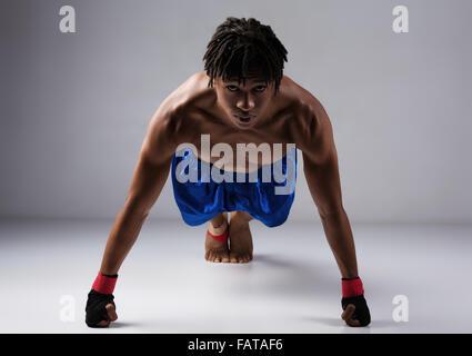 Junge muskulöse athletische männliche Boxer blaue Boxershorts und rote Boxhandschuhe. - Stockfoto