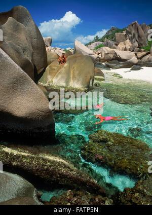Touristen, die Schnorcheln im Gezeiten-Pools auf der Insel La Digue auf den Seychellen - Stockfoto