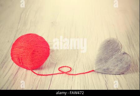 Herz aus Holz mit rotem Garn, Konzept Bild verbunden. - Stockfoto