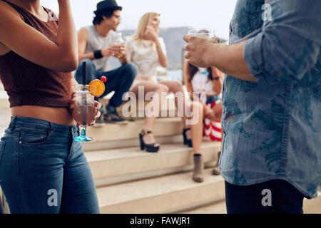 Zugeschnittenen Schuss von ein paar Cocktails Gläser während drei Menschen miteinander zu reden, im Hintergrund halten. Junge Menschen havi