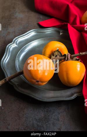 Reife Kaki Früchte auf rustikalen Hintergrund - Stockfoto