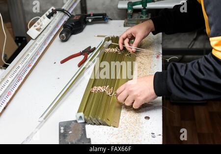 Mann arbeitet auf Montage der Jalousie zu Hause Workshop. - Stockfoto
