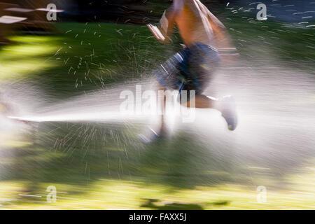 Kleiner Junge läuft durch Sprinkler in der Sommersonne - Stockfoto