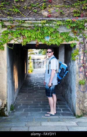 Junge männliche Tourist Rucksack geht unter einem historischen Dorftunnel in Comer See in Sommerkleidung; Varenna, - Stockfoto