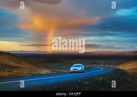 Land straße mit Regenwolken und Regenbogen in der Nähe des Sees Myvatn, Island. - Stockfoto