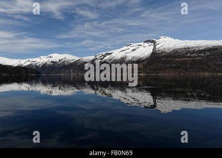 Symmetrische Reflexion von Schnee bedeckt Berge rund um den Hardangerfjord in Westnorwegen. - Stockfoto