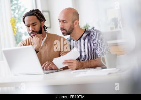 Zwei Männer arbeiten mit Laptop am Tisch zu Hause - Stockfoto