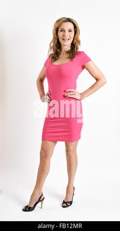 schlanke Frau in rosa körpernahe Kleid auf einem weißen Tropfen - Stockfoto