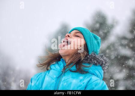 Mädchen nachschlagen, Zunge Schneeflocken fangen - Stockfoto