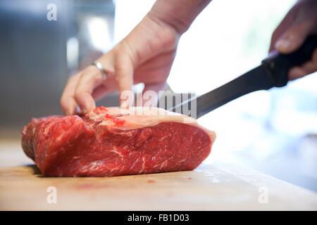 Nahaufnahme von Metzger Hände schneiden rohe Steak auf Metzger block - Stockfoto