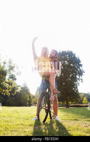 Junges Paar auf sonnenbeschienenen Park Smartphone Selfie am Fahrrad - Stockfoto
