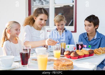 Teenager-Mädchen Beleuchtung Geburtstagskuchen Kerzen für Kinder am Terrassentisch - Stockfoto