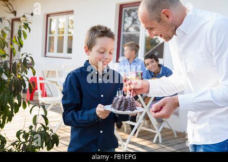 Mitte erwachsenen Mannes Beleuchtung Söhne Geburtstagskuchen Kerzen auf Terrasse - Stockfoto