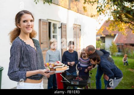 Porträt von Teenager-Mädchen tragen Teller mit gegrilltem Essen am Grill im Garten - Stockfoto
