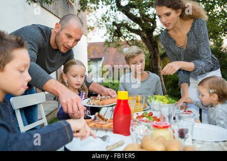 Vater und Teenager-Mädchen Kinderhilfe am Grill im Garten Tisch - Stockfoto