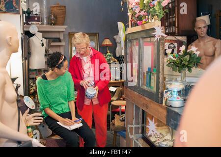 Reife Frau Kunde Prüfung China Topf in Vintage-shop - Stockfoto