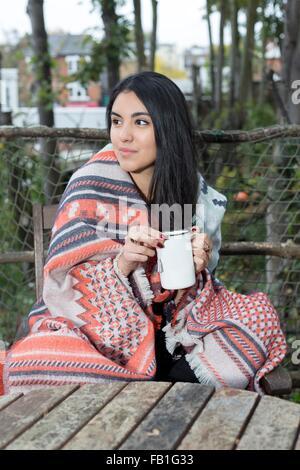 Junge Frau eingewickelt in Decke, Kaffeetrinken, Hampstead Heath, London - Stockfoto