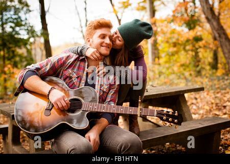 Romantische junges Paar Gitarre spielen auf Picknickbank im herbstlichen Wald - Stockfoto