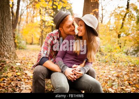 Romantische junges Paar sitzt im herbstlichen Wald - Stockfoto