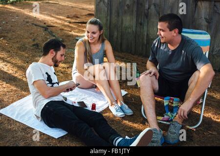 Drei Erwachsenen Freunden entspannende außerhalb der Hütte im Wald - Stockfoto