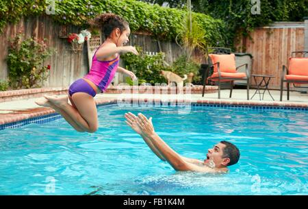 Seitenansicht des Vaters fangen Mädchen Sprung ins Schwimmbad, in der Luft - Stockfoto
