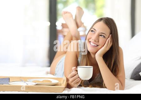 Glückliches Mädchen frühstücken hält eine Kaffeetasse auf dem Bett liegend und auf der Suche nach seitwärts - Stockfoto