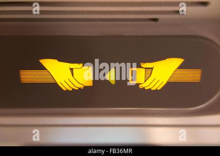 """Flugzeug """"Fasten Seat Belt / Sicherheitsgurt"""" Licht Zeichen leuchtet & beleuchtet während eines Fluges im A320 Flugzeug - Stockfoto"""