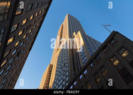 Empire State Building bei Sonnenuntergang von unten. Niedrigen Winkel auf der Art-Déco-Wolkenkratzer befindet sich in Midtown Manhattan, New York.