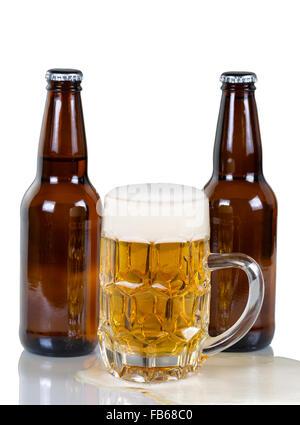 Golden gefärbt Bier fließt aus Glas Becher mit zwei vollen Flaschen im Hintergrund. Isoliert auf weiss mit Reflexion. - Stockfoto
