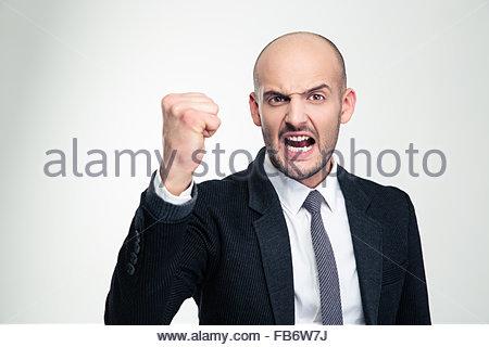 Gereizt, wütend junge Geschäftsmann in festlich gekleidet, schreien und zeigt Faust auf weißem Hintergrund - Stockfoto