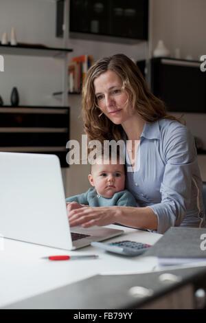 Frau auf Laptop sitzend mit Baby Girl zu Hause arbeiten - Stockfoto